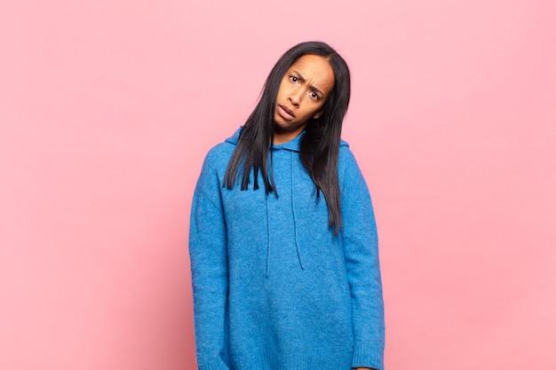 Młoda czarna kobieta czuje się zdezorientowana i zdezorientowana, z tępym, oszołomionym wyrazem twarzy, patrzącą na coś nieoczekiwanego