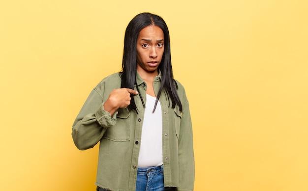 Młoda czarna kobieta czuje się zdezorientowana, zakłopotana i niepewna, wskazując na siebie, zastanawiając się i pytając, kto, ja?