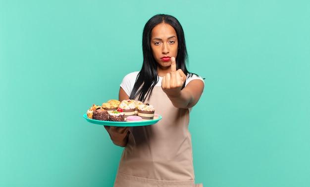 Młoda czarna kobieta czuje się zła, zirytowana, buntownicza i agresywna, machając środkowym palcem, walcząc. koncepcja szefa kuchni piekarni