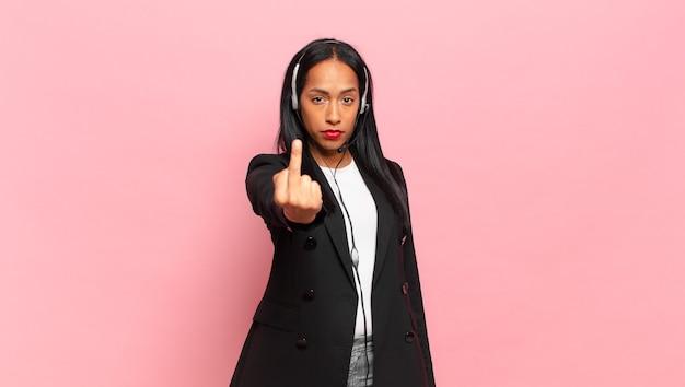 Młoda czarna kobieta czuje się zła, zirytowana, buntownicza i agresywna, machając środkowym palcem, walcząc. koncepcja telemarketingu