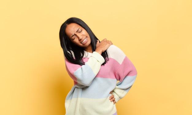 Młoda czarna kobieta czuje się zmęczona, zestresowana, niespokojna, sfrustrowana i przygnębiona, cierpi na ból pleców lub szyi