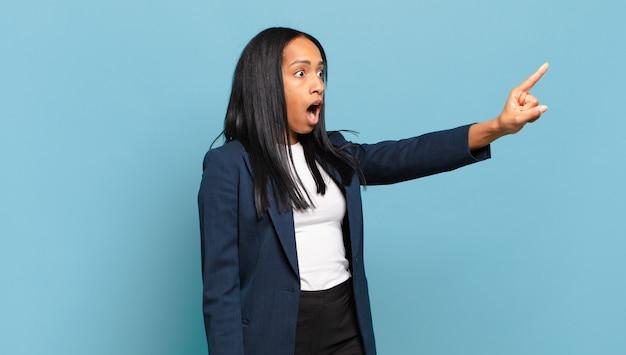 Młoda czarna kobieta czuje się zszokowana i zaskoczona, wskazując i patrząc w górę z podziwem ze zdumionym, otwartymi ustami. pomysł na biznes