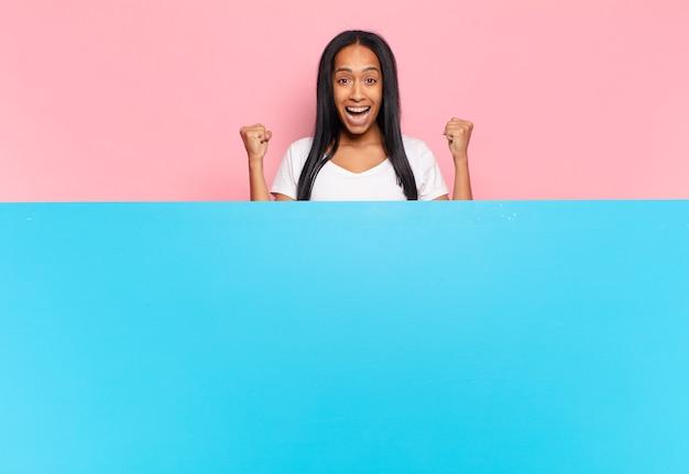 Młoda czarna kobieta czuje się zszokowana, podekscytowana i szczęśliwa, śmiejąc się i świętując sukces, mówiąc wow!. kopia koncepcja przestrzeni
