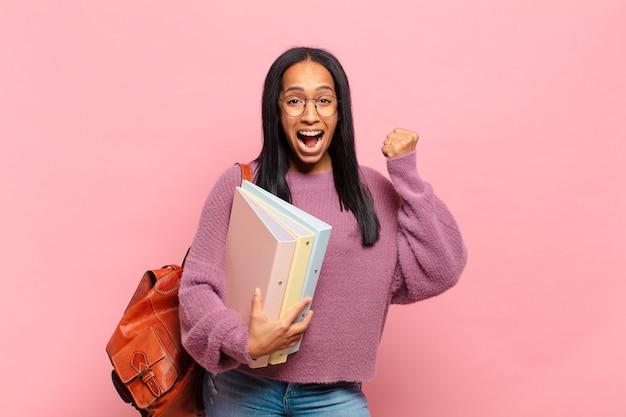 Młoda czarna kobieta czuje się zszokowana, podekscytowana i szczęśliwa, śmieje się i świętuje sukces