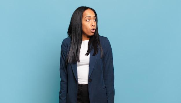 Młoda czarna kobieta czuje się zszokowana, szczęśliwa, zdumiona i zaskoczona, patrząc w bok z otwartymi ustami. pomysł na biznes