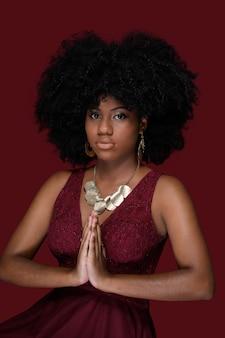 Młoda czarna kobieta dotyka dłoni we włosach afro ben w czerwonej sukience odizolowanej na czerwonym tle
