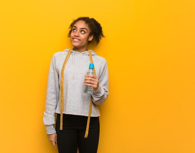 Młoda czarna kobieta fitness marzy o osiągnięciu celów i zamierzeń. trzymając butelkę wody.