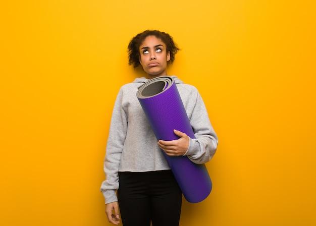 Młoda czarna kobieta fitness zmęczona i znudzona. trzymanie maty.