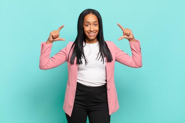 Młoda czarna kobieta kadrowanie lub zarysowanie własnego uśmiechu obiema rękami, patrząc pozytywnie i szczęśliwie, koncepcja odnowy biologicznej. pomysł na biznes