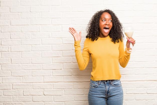 Młoda czarna kobieta krzycząc szczęśliwy, zaskoczony ofertą lub promocją, gapiąc się, skacząc i dumny