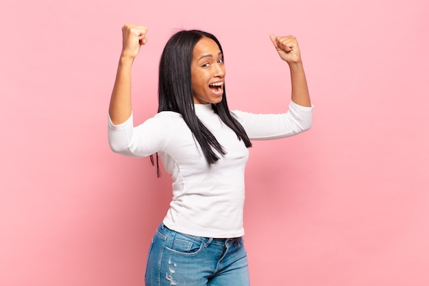 Młoda czarna kobieta krzycząca triumfalnie, wyglądająca jak podekscytowana, szczęśliwa i zaskoczona zwycięzca, świętuje