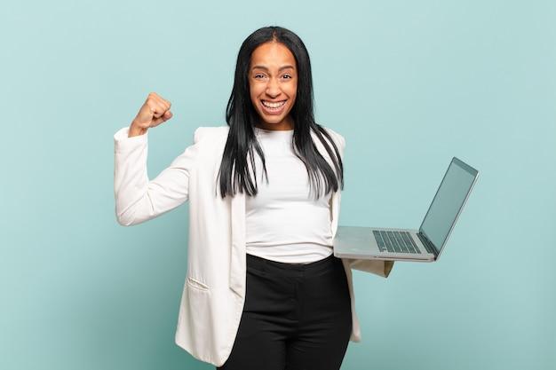 Młoda czarna kobieta krzyczy agresywnie z gniewnym wyrazem twarzy lub z zaciśniętymi pięściami świętując sukces. koncepcja laptopa