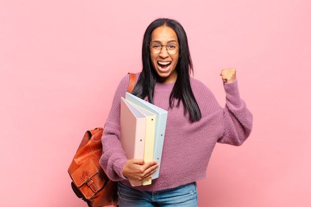 Młoda czarna kobieta krzyczy agresywnie z gniewnym wyrazem twarzy lub z zaciśniętymi pięściami świętując sukces. koncepcja studenta