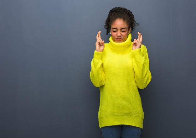 Młoda czarna kobieta krzyżuje palce za szczęście