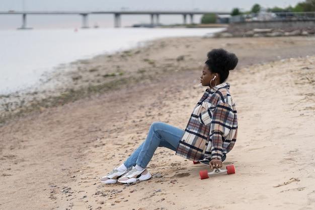 Młoda czarna kobieta milenijna siedzi na plaży nad rzeką na longboardzie, patrząc na wodę, zastanawiając się nad myślami