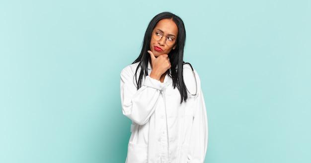 Młoda czarna kobieta myśląca, wątpiąca i zdezorientowana, mająca różne możliwości, zastanawiająca się, którą decyzję podjąć. koncepcja lekarza