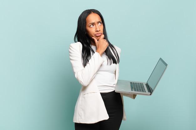 Młoda czarna kobieta myśli, czuje się niepewna i zdezorientowana, ma różne opcje, zastanawia się, jaką decyzję podjąć. koncepcja laptopa