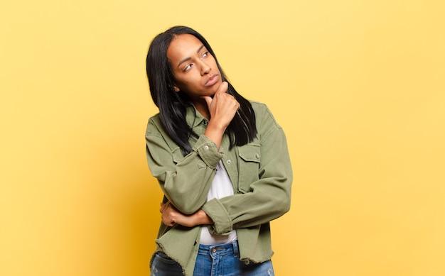 Młoda czarna kobieta myśli, czuje się niepewna i zdezorientowana, ma różne opcje, zastanawia się, jaką decyzję podjąć