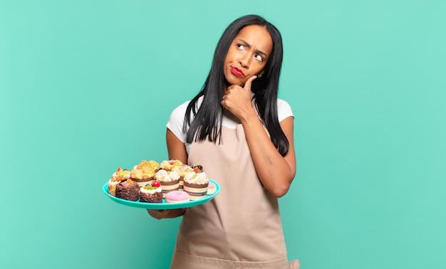Młoda czarna kobieta myśli, czuje się zwątpienie i zdezorientowana, z różnymi opcjami, zastanawiając się, którą decyzję podjąć. koncepcja szefa kuchni piekarni