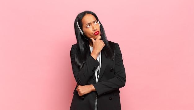 Młoda czarna kobieta myśli, czuje się zwątpienie i zdezorientowana, z różnymi opcjami, zastanawiając się, którą decyzję podjąć. koncepcja telemarketingu