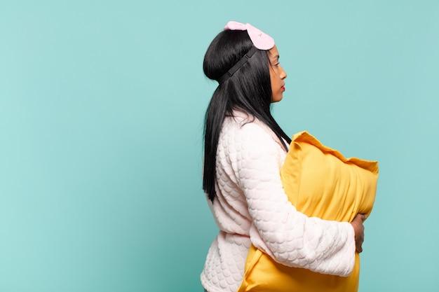 Młoda czarna kobieta na widoku profilu, chcąc skopiować przestrzeń do przodu, myśląc, wyobrażając sobie lub marząc. koncepcja piżamy