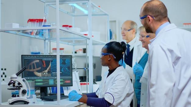 Młoda czarna kobieta naukowiec robi badania medyczne w nowocześnie wyposażonym laboratorium. wieloetniczny zespół badający ewolucję wirusa przy użyciu zaawansowanych technologii do naukowej analizy rozwoju leczenia przeciw covid19.