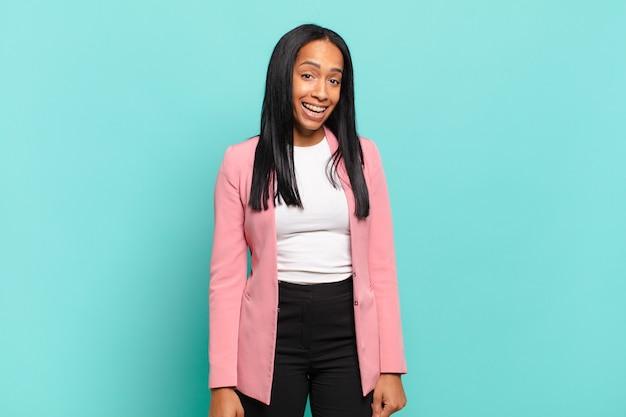 Młoda czarna kobieta o dużym, przyjaznym, beztroskim uśmiechu, wyglądająca pozytywnie, zrelaksowana i szczęśliwa, przerażająca. pomysł na biznes