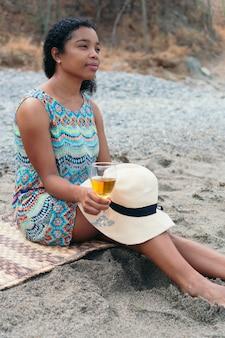Młoda czarna kobieta pije białe wino