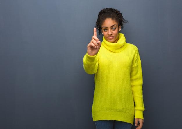 Młoda czarna kobieta pokazuje numer jeden