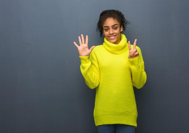 Młoda czarna kobieta pokazuje numer siedem