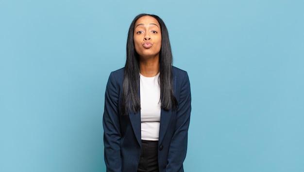 Młoda czarna kobieta ściska usta razem z uroczym, zabawnym, szczęśliwym, uroczym wyrazem twarzy, wysyłając buziaka. pomysł na biznes