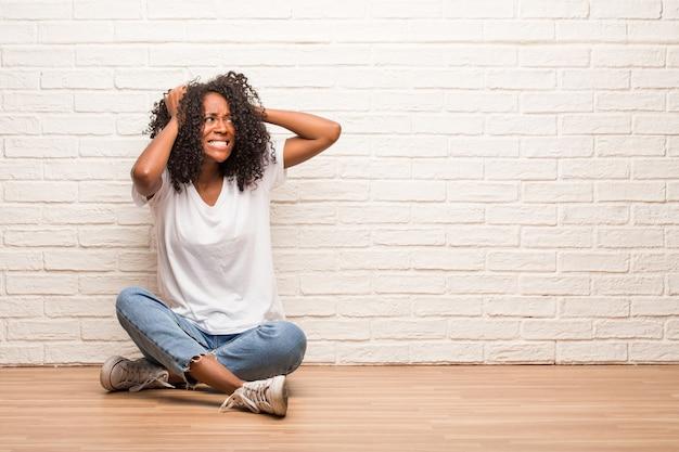 Młoda czarna kobieta siedzi na drewnianej podłodze szalonej i zrozpaczonej, krzycząc z kontroli, śmieszny szaleniec wyrażający wolność i dzikość