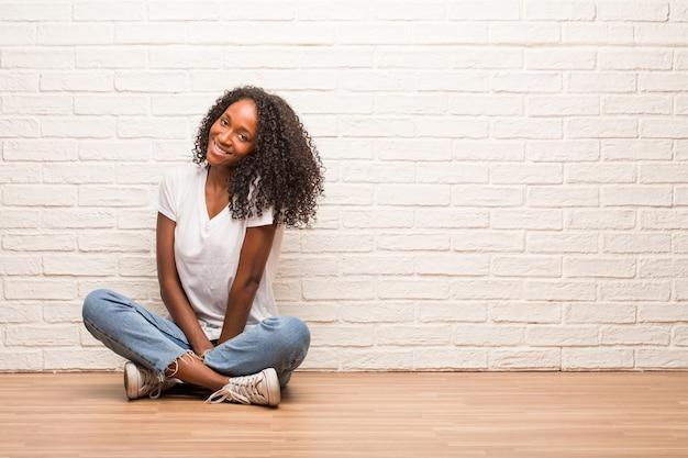 Młoda czarna kobieta siedzi na drewnianej podłodze wesoły iz wielkim uśmiechem, pewny siebie, przyjazny i szczery, wyrażając powodzenie i sukces