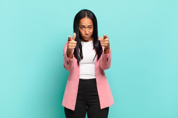 Młoda czarna kobieta skierowana do przodu na aparat palcami i zły wyraz, mówiący, abyś wykonał swój obowiązek. pomysł na biznes