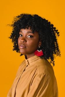 Młoda czarna kobieta stoi bokiem i patrząc na kamery