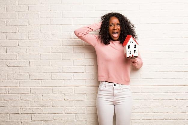 Młoda czarna kobieta szalona i zdesperowana, krzycząca poza kontrolą, zabawna wariatka wyrażająca wolność i dzikość
