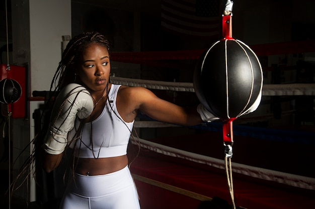 Młoda czarna kobieta trenuje boks w ringu.