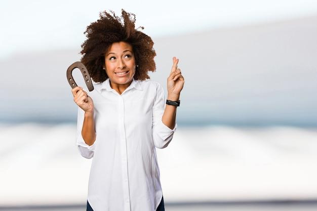 Młoda czarna kobieta trzyma podkowę