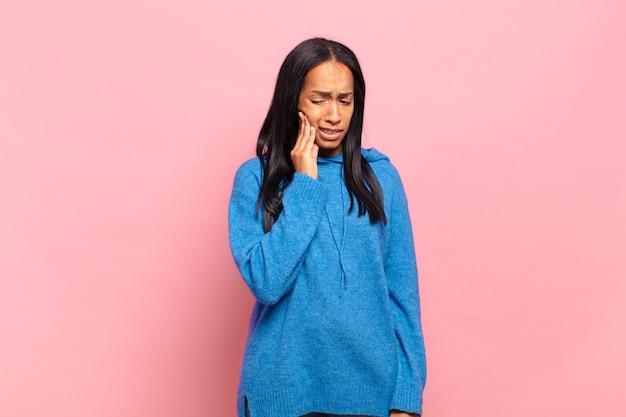 Młoda czarna kobieta trzyma policzek i cierpi na bolesny ból zęba, czuje się chora, nieszczęśliwa i nieszczęśliwa, szuka dentysty