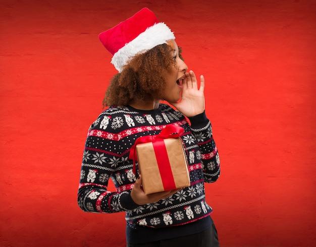 Młoda czarna kobieta trzyma prezent w święto bożonarodzeniowe szepcze plotki tonę