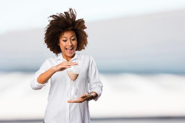 Młoda czarna kobieta trzyma zegar piasku