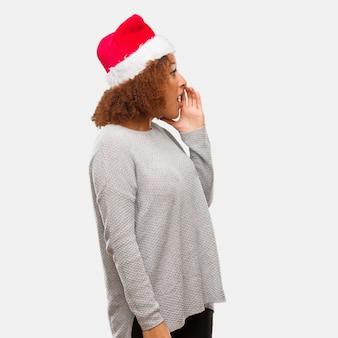 Młoda czarna kobieta ubrana w kapelusz santa szepcząc podszeptować