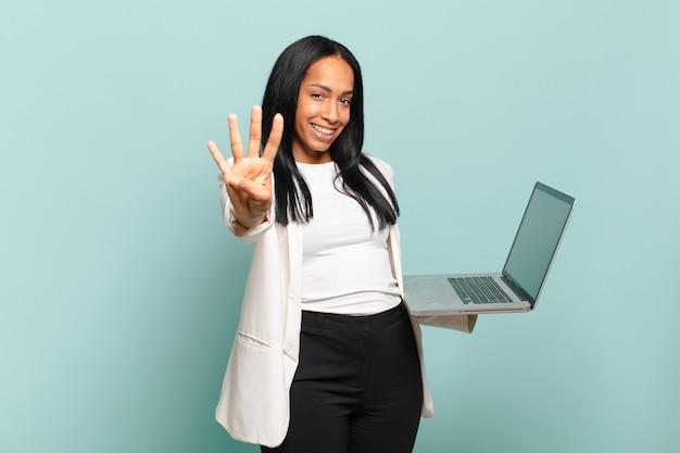 Młoda czarna kobieta uśmiecha się i wygląda przyjaźnie, pokazując numer cztery lub czwarty z ręką do przodu, odliczając. koncepcja laptopa