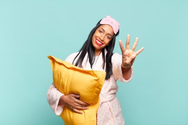 Młoda czarna kobieta uśmiecha się i wygląda przyjaźnie, pokazując numer cztery lub czwarty z ręką do przodu, odliczając. koncepcja piżamy
