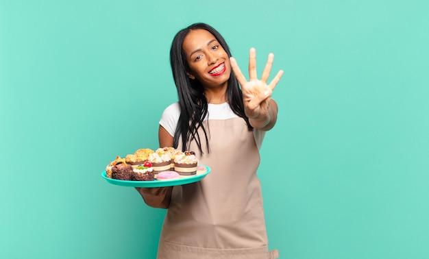 Młoda czarna kobieta uśmiecha się i wygląda przyjaźnie, pokazując numer cztery lub czwarty z ręką do przodu, odliczając. koncepcja szefa kuchni piekarni
