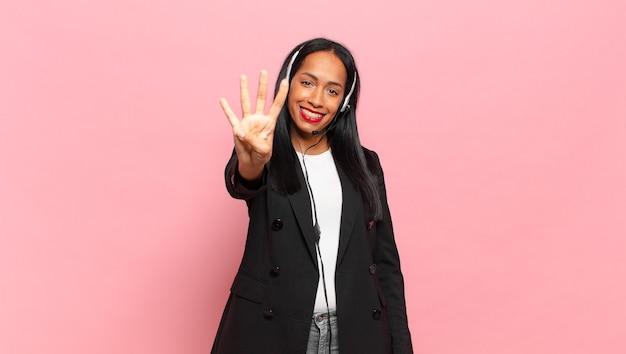 Młoda czarna kobieta uśmiecha się i wygląda przyjaźnie, pokazując numer cztery lub czwarty z ręką do przodu, odliczając. koncepcja telemarketingu
