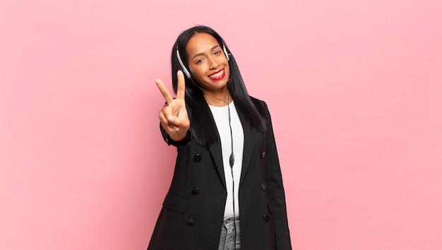 Młoda czarna kobieta uśmiecha się i wygląda przyjaźnie, pokazując numer dwa lub sekundę z ręką do przodu, odliczając. koncepcja telemarketingu