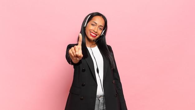Młoda czarna kobieta uśmiecha się i wygląda przyjaźnie, pokazując numer jeden lub pierwszy z ręką do przodu, odliczając. koncepcja telemarketingu
