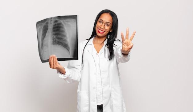 Młoda czarna kobieta uśmiecha się i wygląda przyjaźnie, pokazując numer trzy lub trzeci z ręką do przodu, odliczając. koncepcja lekarza