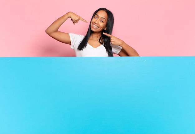 Młoda czarna kobieta uśmiecha się pewnie, wskazując na swój szeroki uśmiech
